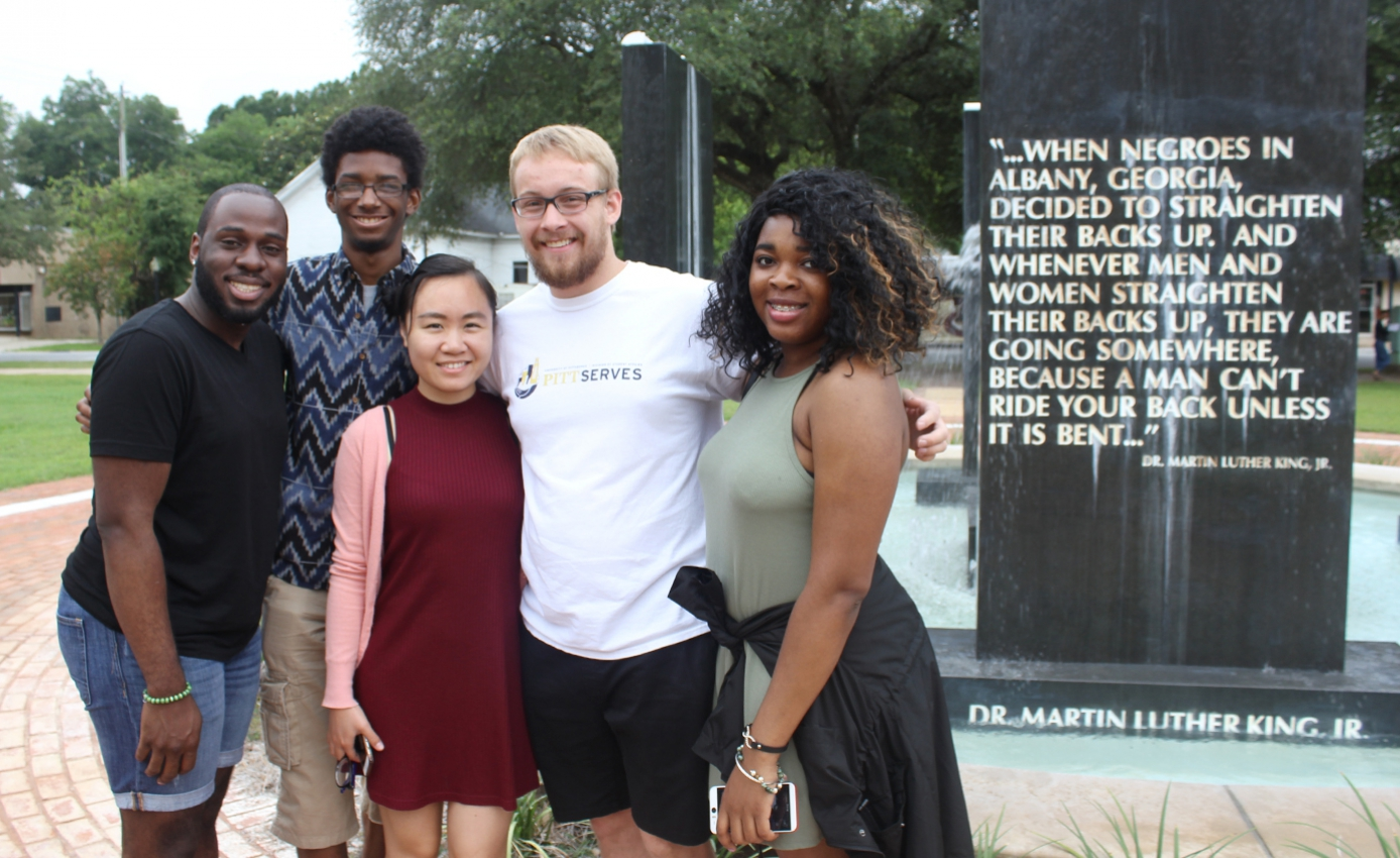 Five students next to an MLK quotation status