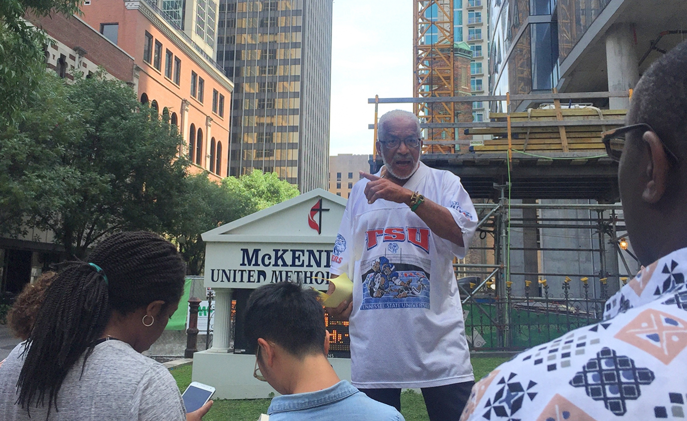 Man in a TSU shirt speaking to a crowd