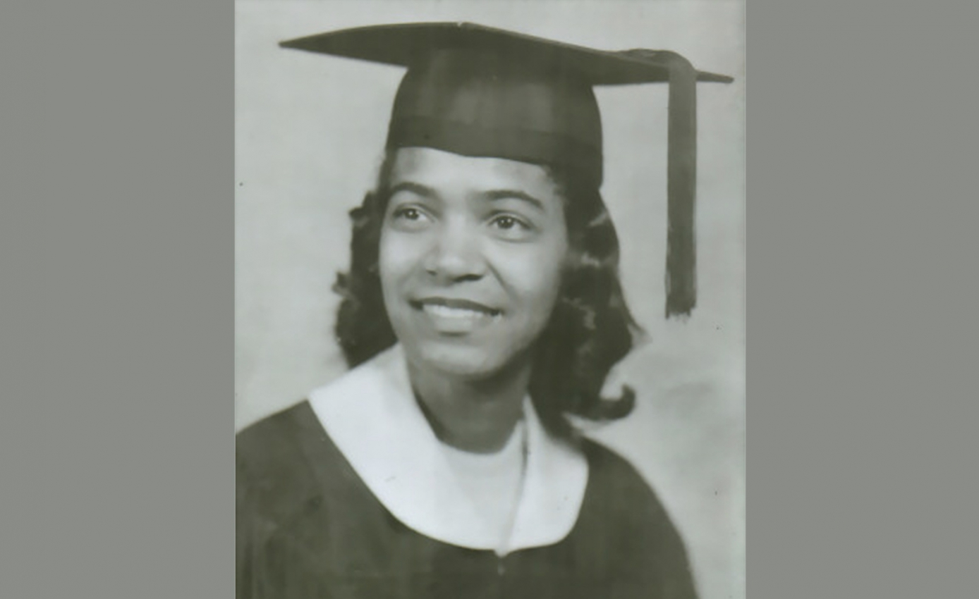 A black and white photo of a woman in a graduation cap and gown