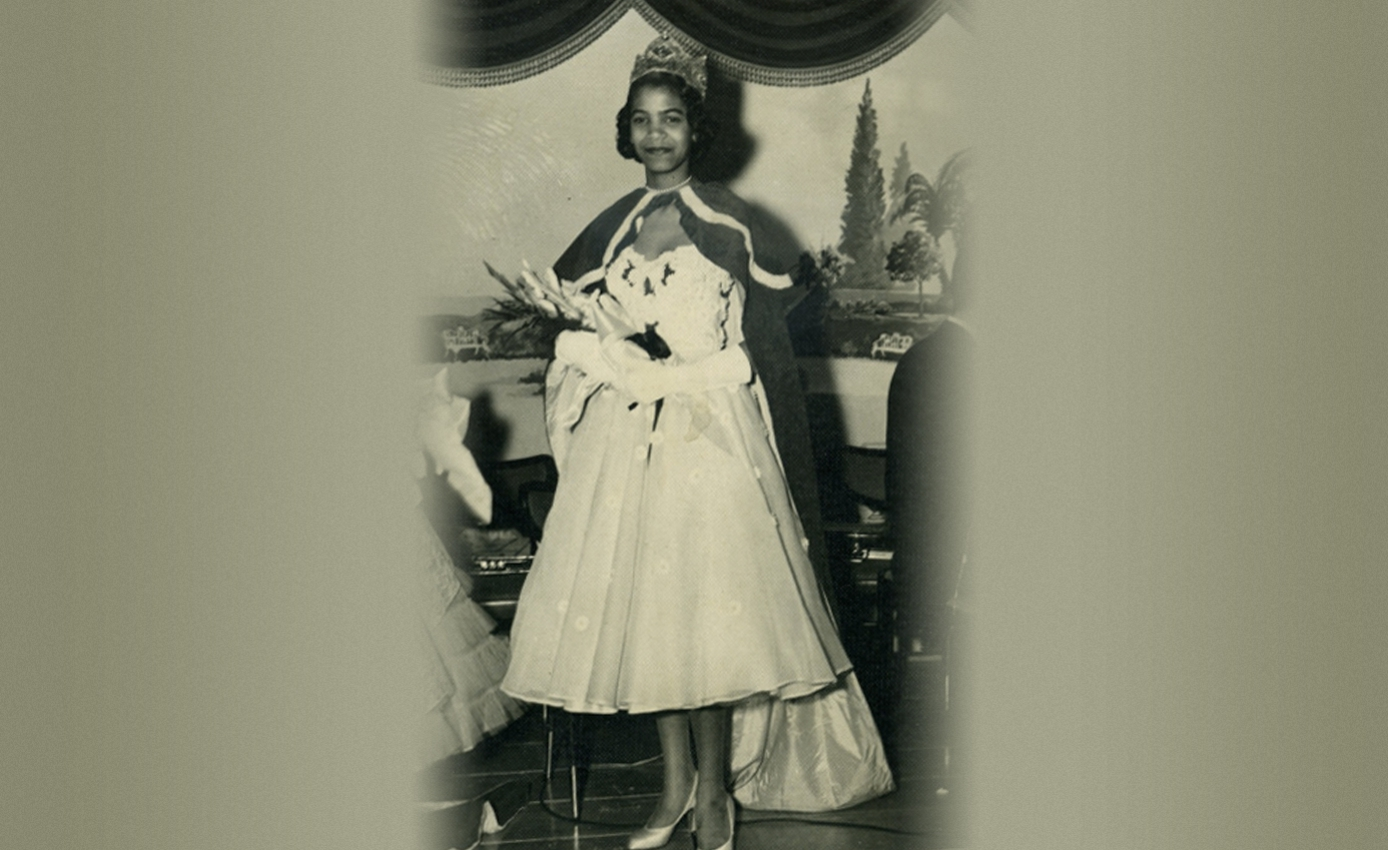 A black and white photo of a woman in a dress, cape and tiara holding flowers