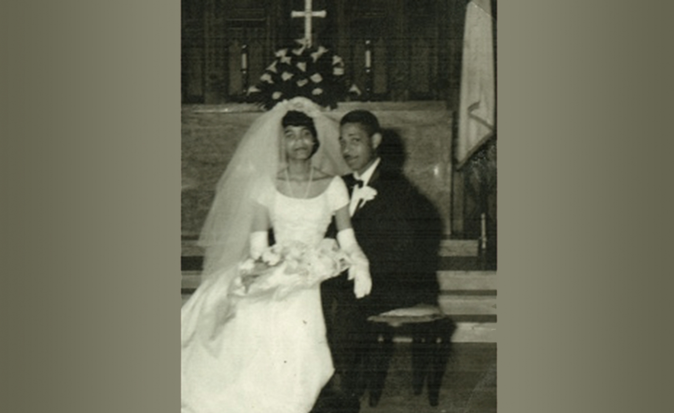 A black and white photo of a woman in a wedding dress seated on the lap of a man in a suit