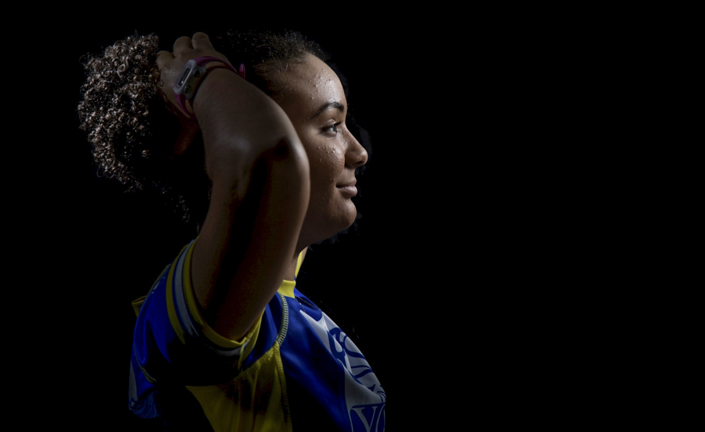 young woman in blue and gold shirt putting up a ponytail, facing right