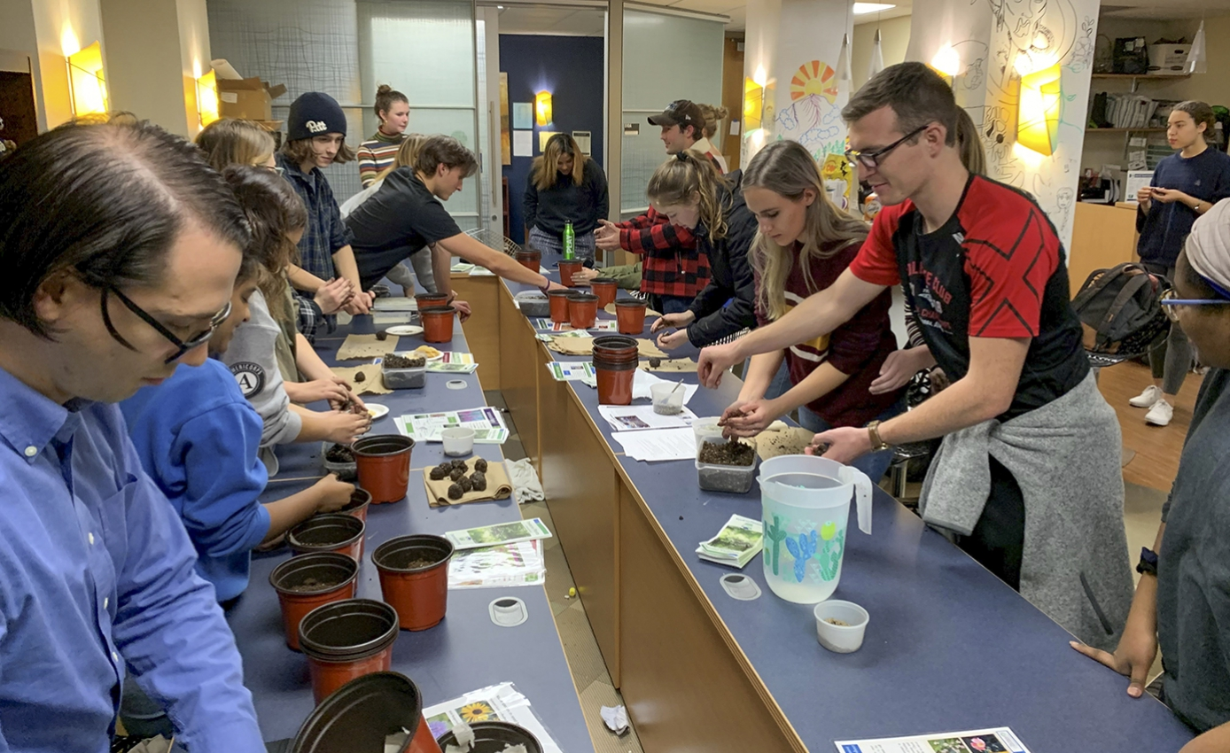 Several people work on potting and planting seeds around a long rectangular blue table.