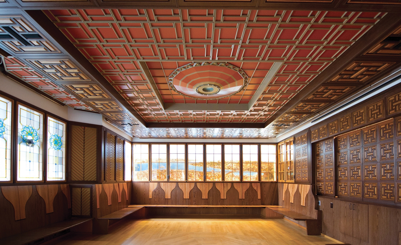 A brown and red room with wooden seats along the walls