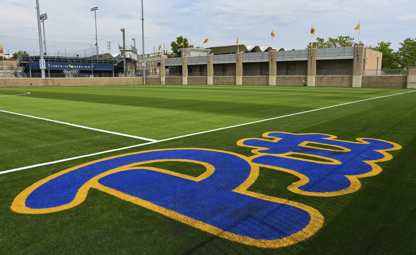 Soccer field with large script PItt wordmark in the foreground on the side of the field.