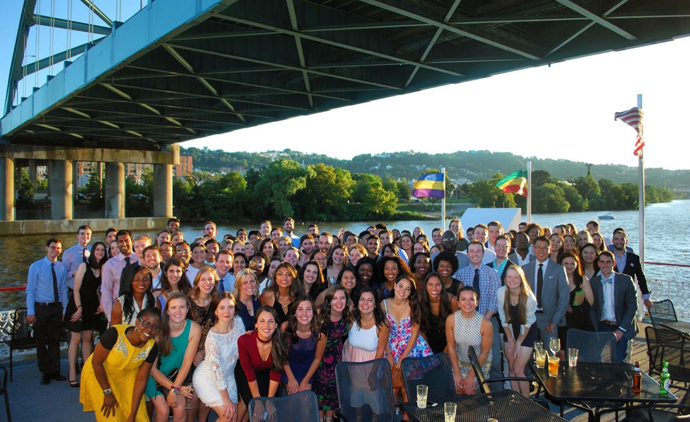 The Pitt Med class of 2021 underneath a bridge in front of a body of water