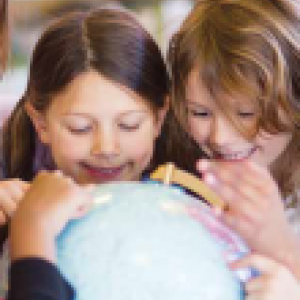 Several children looking at a globe