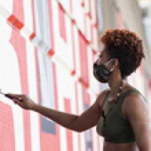 a Black woman painting a large mural
