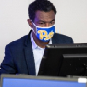 Faculty member in a Pitt mask on a classroom computer.