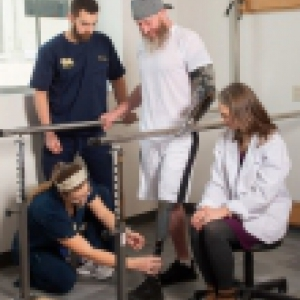 Several students work on a man's prosthetic leg as an instructor observes