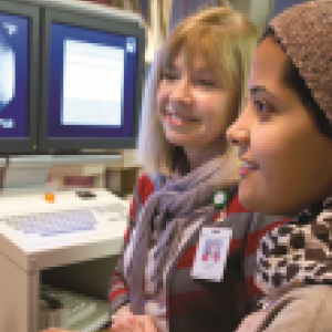 A HIS Student and instructor both look at a set of screens displaying health information
