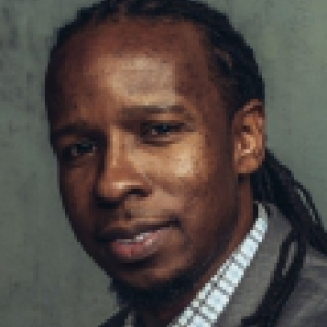 Ibram X. Kendi in a gray suit