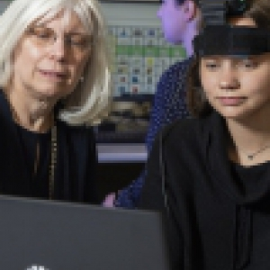 An instructor pointing out something to a student on a laptop