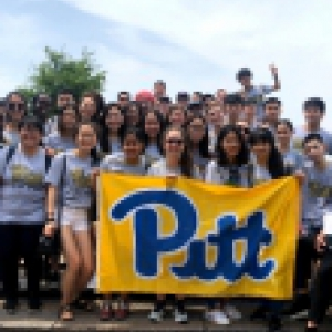 Pitt to You program students holding up a Pitt flag