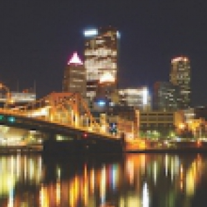 Image of Pittsburgh at night with the buildings fully lit