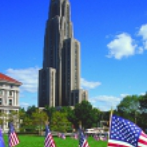 The Cathedral of Learning with small American flags in the foreground