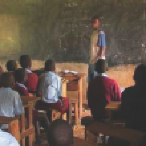 Teacher standing in front of African classroom