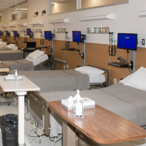 a simulated nursing environment with rows of beds and monitors