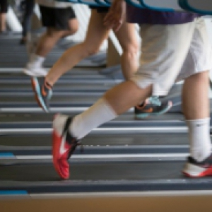People running on treadmills in athletic clothes