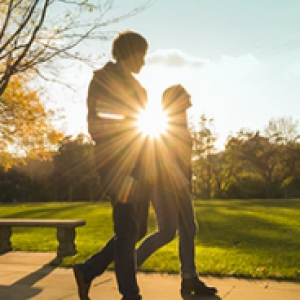 Two people walk on Pitt's campus with the sun shining behind them