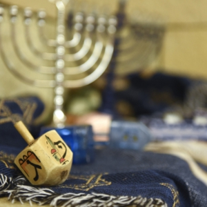 a menorah and dreidel atop a blue cloth