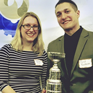female and male students with a trophy