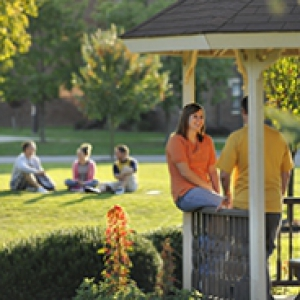 students sitting on a gazebo railing
