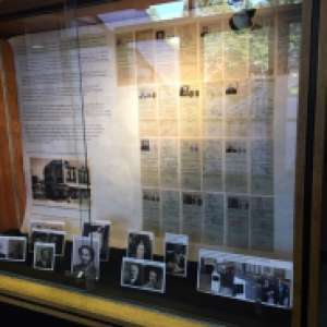 photos and papers arranged in a display case
