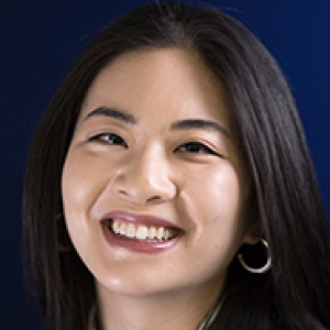 Peggy Liu in a dark jacket against a dark blue background