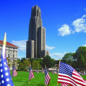 The Cathedral on a blue sky day with American flags planted in the foreground yard