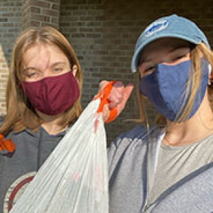 Two women, one in a red mask and another in a blue mask and baseball cap, hold up a trash bag