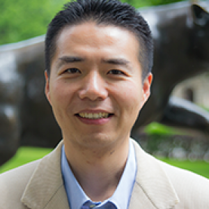 Wang in a tan coat and blue shirt in front of a panther statue
