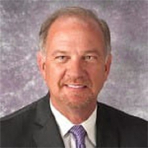 Donal Yealy in a black suit and white shirt with a purple tie