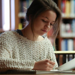 A woman in a sweater writing in a notebook