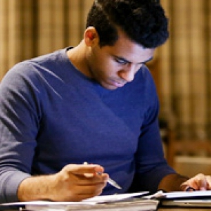 A student in a blue shirt writing