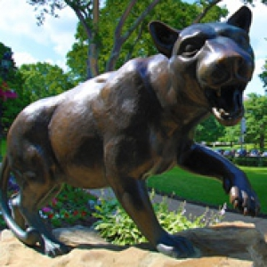 Bronze panther statue with red flowers at its base