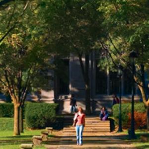 A student walking on a sidewalk
