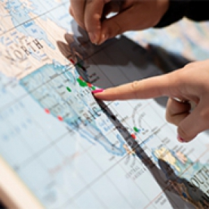 Finger pointing at map