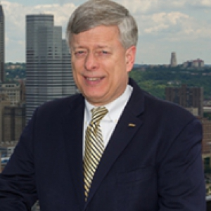 Mark A. Nordenberg in a black suit and a yellow and black striped tie stands on an overlook of Pittsburgh.