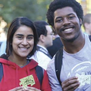 two students holding gold puzzle pieces