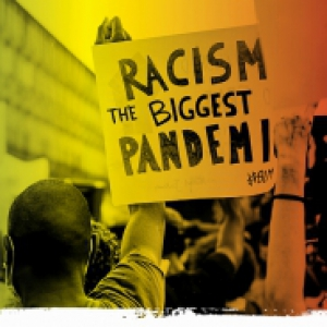 "A black and white image overlaid with green, yellow and red tint, of a protest. A person is holding a sign that says ""Racism is the biggest pandemic"""