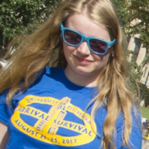 Young woman with blonde hair wearing Pitt Arrival Survival T-shirt and sunglasses