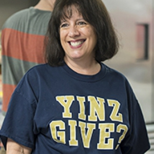 woman in a blue and gold shirt that says Yinz Give?