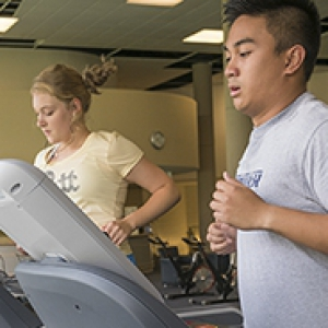 Female and male students running on treadmills