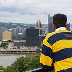 Pitt Pathfinder student wearing blue and gold striped rugby shirt looks out over the city of Pittsburgh skyline