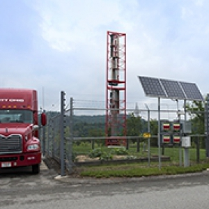 Red tractor trailer parked beside solar and wind power facilities