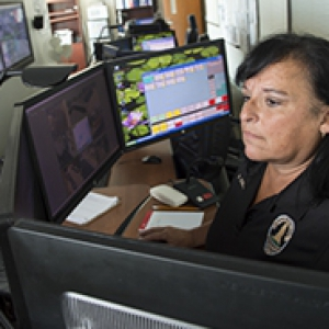 woman in a public safety shirt sitting in front of many monitors