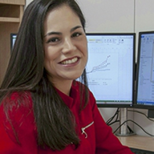 Hernandez in a red blouse in front of computer monitors