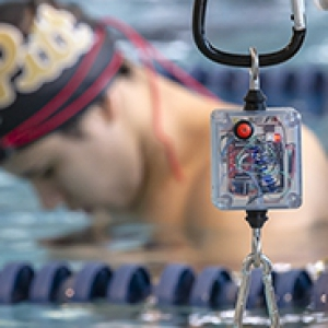 tether device in foreground with swimmer in pool in the background wearing script Pitt swim cap