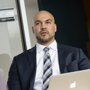 a person in a suit in front of a laptop